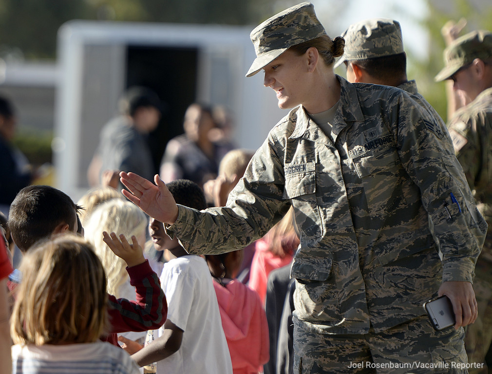 . United States Air Force Senior Airman, Rebecca Berggen high-fives students from Scandia Elementary School Tuesday during the 12th annual Remembrance Walk.