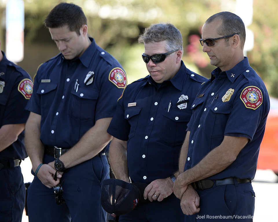. Vacaville Fire Department personnel (from left) firefighter/paramedic, Matt Moreno. firefighter/engineer Tad Samolis and battalion chief, Alex Nourot bow their heads during a moment of silence at a 9/11 ceremony Tuesday held at the city�s 9/11 Memorial right outside the steps of the police department.