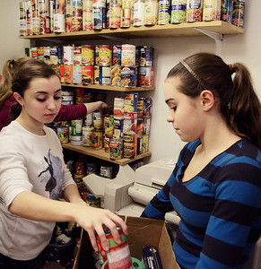 Erica Miller @togianphotog- The Saratogian,   Triplets Lauren (left) and Rachel Venditti, 16 year old Sophomores at SSHS, stocked the shelves at Shelters of Saratoga. Monday Jan. 20th, 2014, in celebration of Martin Luther Kings Day, the community gathered to help local non-for-profits in the city.