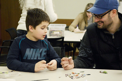 Erica Miller @togianphotog- The Saratogian,   At the Saratoga Springs Public Library, Monday Jan. 20th, 2014, in celebration of Martin Luther Kings Day, the community gathered to help local non-for-profits in the city. On the children's floor they made beads to help provide water to families in Tanzaria. They make paper beads and with every 20 beads made, someone at a school or village will gain access to safe water. Alex Chaucer and his son Sam, 6 years old from Greenfield, looked over their creations.