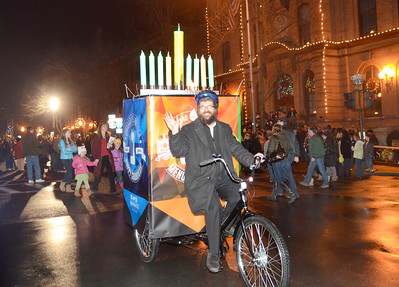 Ed Burke - The Saratogian 12/5/13 On the last night of of Chanukah Rabbi Abba Rubin of Chabad Saratoga pedals his mobile menorah and dreidel down Broadway during Thursday's Victorian Streetwalk in downtown Saratoga Springs.
