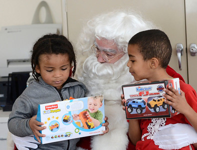 Ed Burke - the Saratogian 12/21/13 Three year old Jaden Harrington, left, and five year old Ja'lique Brown of Vanderbilt Terrace receive gifts Saturday at Saratoga Springs Recreation Center during a party with Santa for children from Vanderbilt and Jefferson Terrace. The event was sponsored by Junior Chamber International.