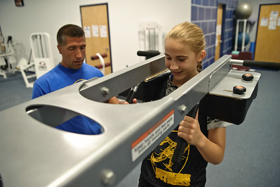 Eric Jenks - The Saratogian Sophia Leveroni squats with supervision of personal trainer Steve Hart during an off season training session at Torres XTF Health and Fitness in Ballston Lake Wednesday, August 6th, 2014.