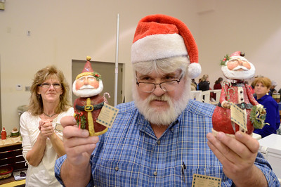 Ed Burke - The Saratogian 11/30/13 Don Cornell of Schoharie poses with paper mache folkart Santa's made by his wife Kathy, seen at left. The couple were selling the items Saturday at the annual craft fair at the City Center to benefit the Saratoga Center for the Family.