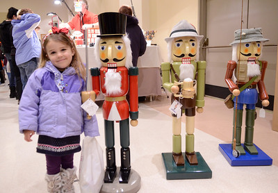 Ed Burke - The Saratogian 11/30/13 Three year old Violet Konanec Noxon of Saratoga Springs stands with wooden nutcrackers made by Darrel Altizer of Peru, N.Y. at his booth Saturday at the annual craft fair at the City Center to benefit the Saratoga Center for the Family.