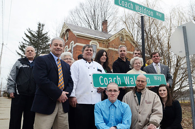 Erica Miller @togianphotog - The Saratogian:  On Friday April 4th, 2014, the city of Saratoga Springs dedicated the late Ray Waldron with a street sign replacing Pleasant Street to Coach Waldron Way. Family members posed for a photograph after the presentation.