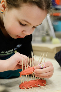 "Erica Miller @togianphotog - The Saratogian:  On Thursday morning, February 27th, 2014, kindergartners in Mrs. Allison Girard's classroom (maternity substitute teacher) at Lake Ave Elementary, students worked on building homes with play dough, sticks and glue. The class is the only pilot school in NYS for the pre-engineering program Project Lead the Way. The class read the ""three little pigs"" and tried to build their own houses to test against a fan. Rebekah Rich pieced toothpicks into play dough to create their house."