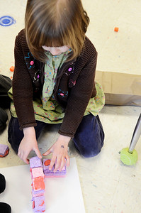 "Erica Miller @togianphotog - The Saratogian:  On Thursday morning, February 27th, 2014, kindergartners in Mrs. Allison Girard's classroom (maternity substitute teacher) at Lake Ave Elementary, students worked on building homes with play dough, sticks and glue. The class is the only pilot school in NYS for the pre-engineering program Project Lead the Way. The class read the ""three little pigs"" and tried to build their own houses to test against a fan. Miriam Hrbek works on piecing together sponges with play dough."