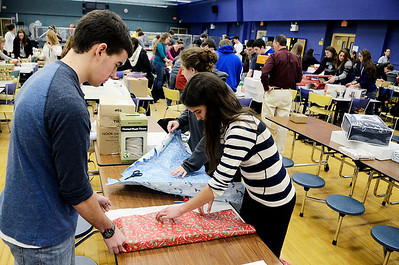 Erica Miller @togianphotog	- The Saratogian.     The Saratoga Springs High School National Honor Society wrapped over a thousand presents Wednesday night. The Be A Santa to a Senior program, their 10th year, is put together through the Home Instead Senior Care. All gifts were requested through the seniors on a Senior Tree ornament.  Twins Cameron and Maya Bain, 16 year old Juniors, wrap a gift in the school cafeteria.SAR-l-SantaSenior2