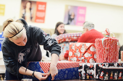 Erica Miller @togianphotog- The Saratogian.     The Saratoga Springs High School National Honor Society wrapped over a thousand presents Wednesday night. The Be A Santa to a Senior program, their 10th year, is put together through the Home Instead Senior Care. All gifts were requested through the seniors on a Senior Tree ornament.  Mackenzie Gaze, 17 year old Senior, wrap a gift in the school cafeteria.SAR-l-SantaSenior5