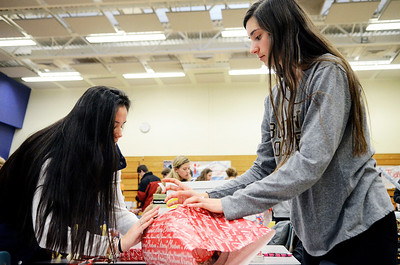 Erica Miller @togianphotog	- The Saratogian.     The Saratoga Springs High School National Honor Society wrapped over a thousand presents Wednesday night. The Be A Santa to a Senior program, their 10th year, is put together through the Home Instead Senior Care. All gifts were requested through the seniors on a Senior Tree ornament.  Ellery Bianco (left) and Claudia Heritage 16 year old Juniors, wrap a gift in the school cafeteria.SAR-l-SantaSenior3