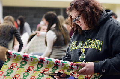Erica Miller @togianphotog- The Saratogian.     The Saratoga Springs High School National Honor Society wrapped over a thousand presents Wednesday night. The Be A Santa to a Senior program, their 10th year, is put together through the Home Instead Senior Care. All gifts were requested through the seniors on a Senior Tree ornament.  Robin Eads, 17 year old Senior, wrap a gift in the school cafeteria.SAR-l-SantaSenior6
