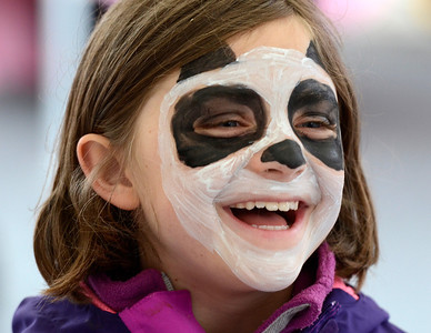 Eight year old Cassidy Samuels reacts after seeing her freshly painted panda face in a mirror during Saturday's Tree Toga celebration on Henry St.