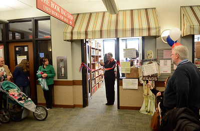 Ed Burke - The Saratogian 04/05/14 Saratoga Springs Public Library Director A. Issac Pulver looks on at Mayor Joanne Yepsen cuts the ribbon officially opening The Book Bag used book store which is run by the Friends of SSPL. Ribbon cuttings also happened Saturday for the renovated teen room and the library cafe now run by the nearby Bread Basket Bakery and will open officially later this week.