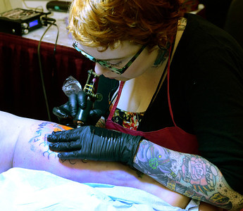 Ed Burke - The Saratogian 04/05/14 Tattoo artist Rhiannon of Albany works on Laura Stella, also of Albany, Saturday at the Saratoga Tattoo Expo at the city center.