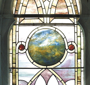 An circular pane of stained glass suggests an abstract  earth and sky design in one of the original windows at Universal Preservation Hall. Ed Burke 4/14/06