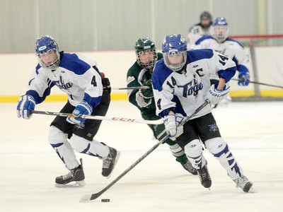 Ed Burke - The Saratogian 02/06/14; Saratoga's Drew Patterson moves the puck as teammate Jack Rittenhouse looks on during Thursday's varsity hockey matchup at Saratoga Springs Ice Rink.