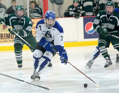 Ed Burke - The Saratogian 02/06/14; Saratoga's Devin Coffey lines up a shot as Shen's John Cady (12) and  Tucker Marvin Look on during Thursday's varsity hockey matchup at Saratoga Springs Ice Rink.