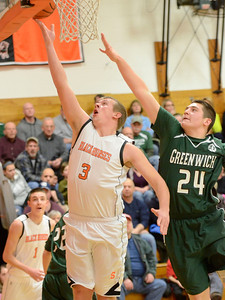 Ed Burke - The Saratogian 02/07/14; Schuylerville's Nick Richard gets two as Greenwich defender George Ostrowski tries to block during Friday's matchup in Schuylerville.