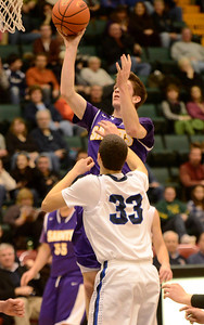 Ed Burke - The Saratogian 02/26/14 Saratoga Central Catholic's Mike Naughton goes to the basket over Lake George defender Duncan Mularz during Wednesday's Class C semi-final in Glens Falls.