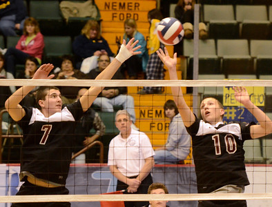 Ed Burke - The Saratogian Burnt Hills-Ballston Lake volleyball players Riley Hynes (7) and Dan Symer reach for the ball during Friday's state volleyball championships at the Glens Falls Civic Center.
