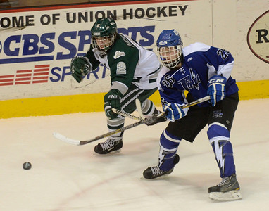 Ed Burke - The Saratogian 02/25/14 Saratoga's Elliott Hungerford clears the puck from the zone as Shen's Ryan Mortka pressures.