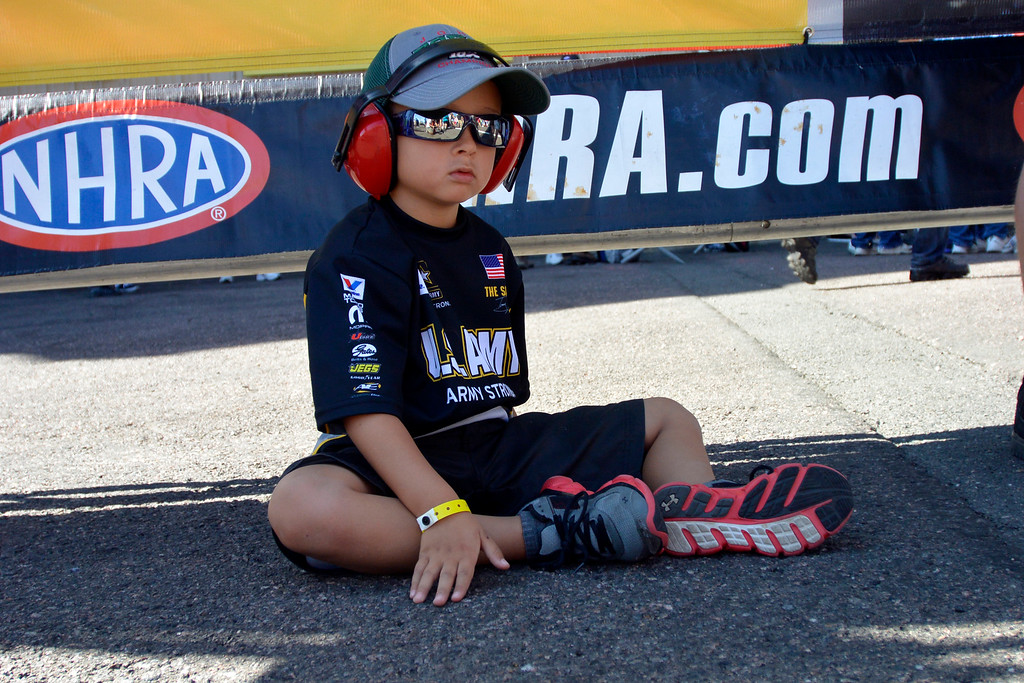 . Colin Kamada 5, sits off to the side with ear protectors on during the pre race festivities at the Mopar Mile-High NHRA Nationals July 21, 2013 at Bandimere speedway in Morrison. (Photo By John Leyba/The Denver Post)