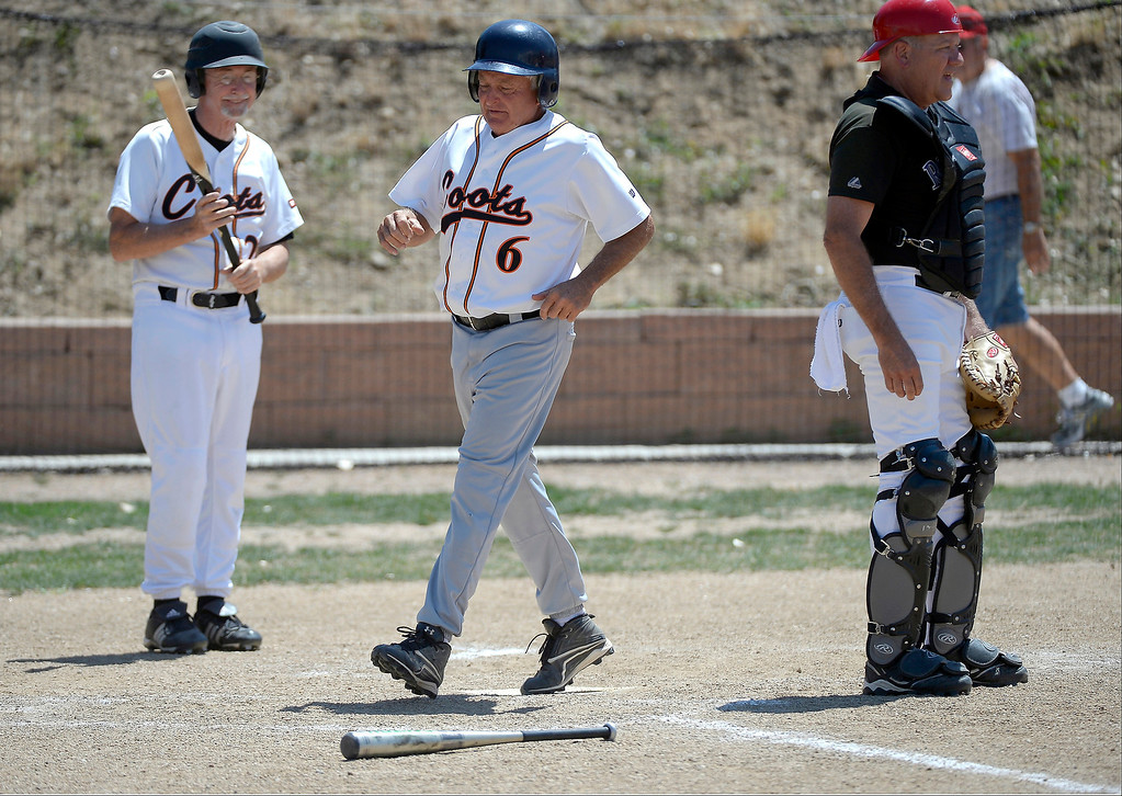. Jerry Malberg of the Coots team crosses the plate for a score during their game at the old Mapleton High School fieldy. Mark Danuser has used his own money to create the baseball playing field and training facility in this north Denver neighborhood. (Photo By John Leyba/The Denver Post)