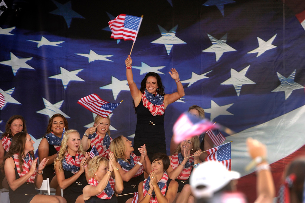 . American golfer Gerina Piller waved a flag as she was introduced Thursday. Following a final practice round at the Colorado Golf Club the United States team and the team from Europe participated in opening ceremonies to being competition for the Solheim Cup Thursday evening, August 15, 2013. Photo By Karl Gehring/The Denver Post