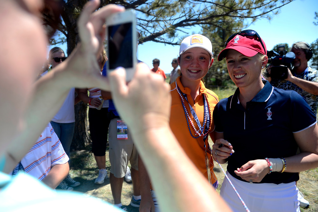 . Libby Singleton, 13, poses with Morgan Pressel as her mother, April Singleton, takes a picture during a practice round for the Solheim Cup. The United States has never lost on a home course. (Photo by AAron Ontiveroz/The Denver Post)