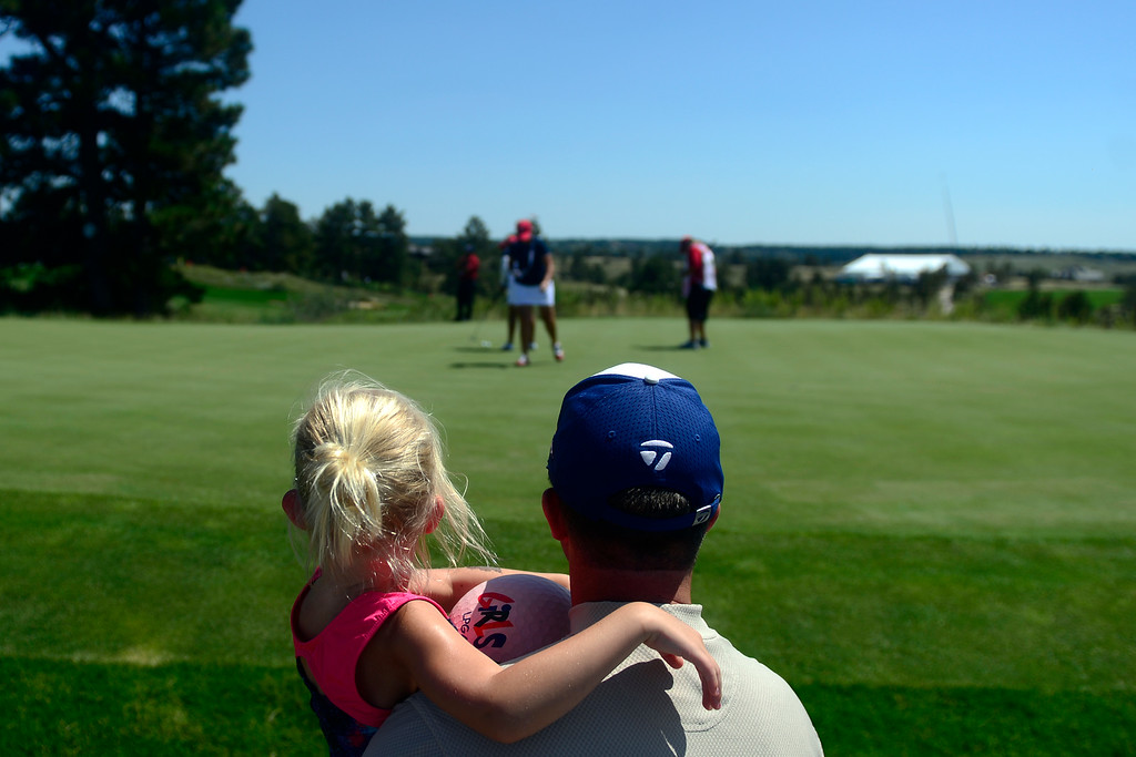 . Jason Blanchard holds his daughter, Addison, 4, as they watch the U.S. team on the green during a practice round for the Solheim Cup. The United States has never lost on a home course. (Photo by AAron Ontiveroz/The Denver Post)