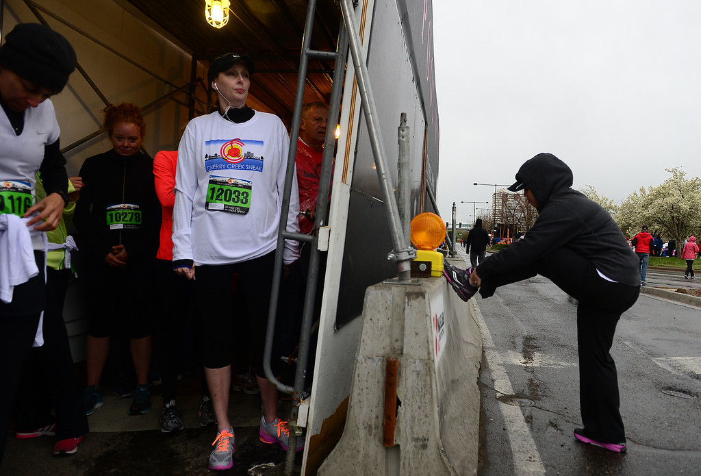 . Melissa Conte, left, tries to stay warm and dry under construction scaffolding before the start of the 5k of the 32nd annual Cherry Creek Sneak in Denver on April 27, 2014.     (Photo By Helen H. Richardson/ The Denver Post)