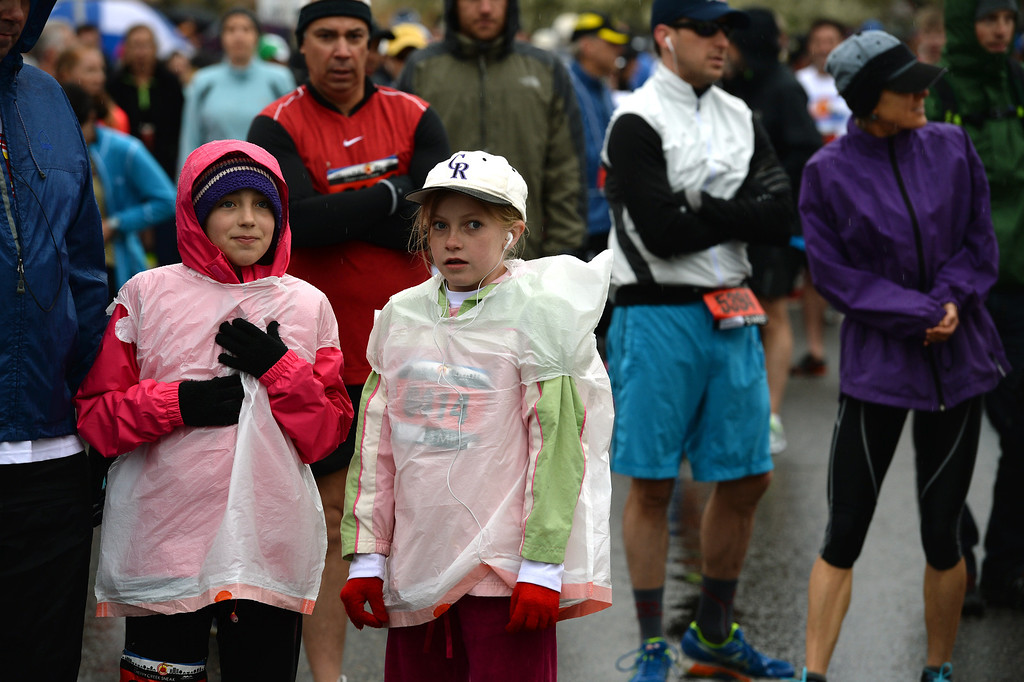 . Megan Peppin, 9, left and Megan Wilcox, 9, middle, try to stay warm and dry under plastic wrap as they line up with other runners before the start of the 5 mile race in the 32nd annual Cherry Creek Sneak.  (Photo By Helen H. Richardson/ The Denver Post)