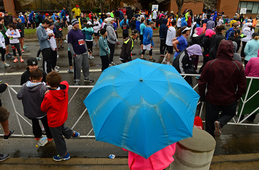 . Runners warm up and try to stay dry before the start of the 5-mile race in the 32nd annual Cherry Creek Sneak in Denver.  (Photo By Helen H. Richardson/ The Denver Post)