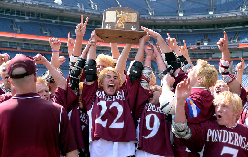 . Senior attack Blake Bruner held the championship trophy as the Mustangs began the celebration Saturday. The Ponderosa High School boy\'s lacrosse team defeated Wheat Ridge 13-11 in the 4A championship game Saturday afternoon, May 17, 2014. (Photo by Karl Gehring/The Denver Post)