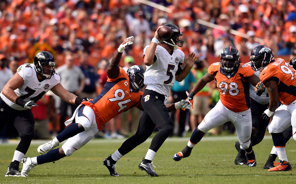 . Joe Flacco (5) of the Baltimore Ravens throws and gains 5 yards while DeMarcus Ware (94) of the Denver Broncos comes in and tries for the sack during the second quarter.  The Denver Broncos played the Baltimore Ravens at Sports Authority Field at Mile High in Denver, CO on September 13, 2015. (Photo by Helen H. Richardson/The Denver Post)