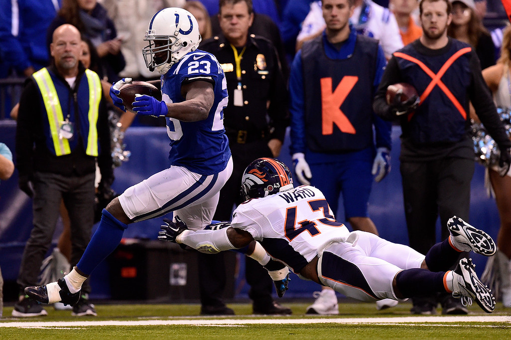 . Frank Gore (23) of the Indianapolis Colts makes a first down as T.J. Ward (43) of the Denver Broncos dives for the stop during the first half of play at Lucas Oil Stadium. The Indianapolis Colts hosted the Denver Broncos on Sunday, November 8, 2015. (Photo by AAron Ontiveroz/The Denver Post)