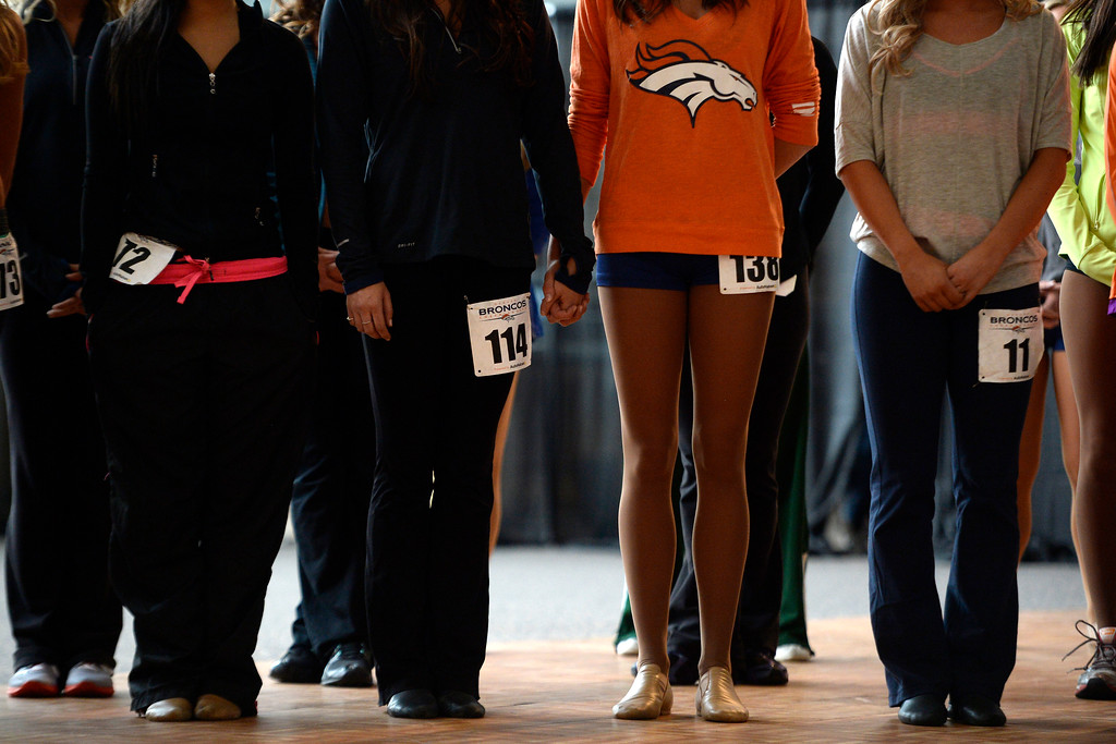 . Competitors  hold hands as they wait to hear their numbers called during tryouts for the 2014-2015 Denver Broncos cheerleaders. More than 100 women showed up and 57 finalists were selected for the 26 spots on the team at Sports Authority Field at Mile High on Sunday, March 30. (Photo By AAron Ontiveroz/The Denver Post)