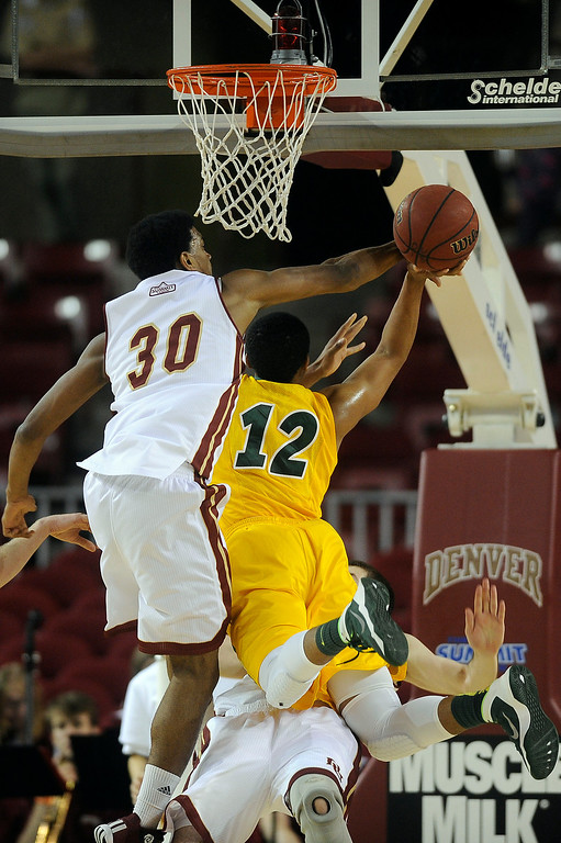 . University of Denver guard Cam Griffin (30) swats the ball out of North Dakota State guard Lawrence Alexander (12) as he Alexander drives to the net during the first half at Magness Arena in Denver, Colorado on February 1, 2014. (Photo by Seth McConnell/The Denver Post)