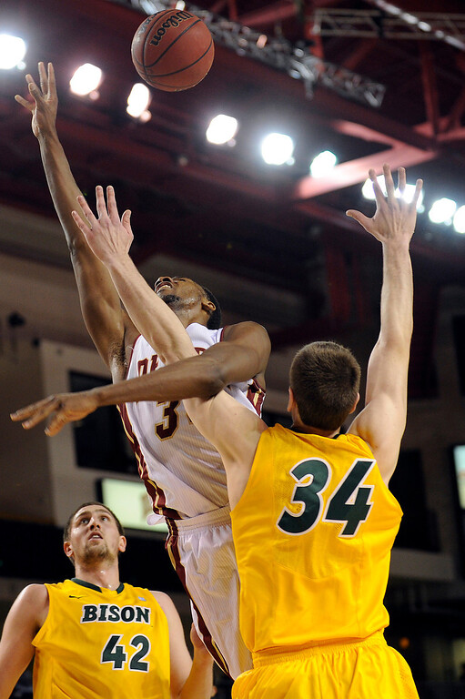 . University of Denver forward Chris Udofia (34) is fouled by North Dakota State forward Chris Kading (34) as he drives to the net during the first half at Magness Arena in Denver, Colorado on February 1, 2014. (Photo by Seth McConnell/The Denver Post)