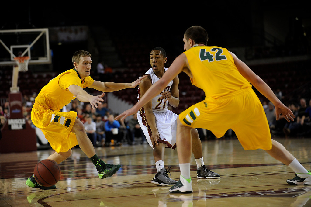 . University of Denver guard Bryant Rucker (21) splits the North Dakota defense as he passes to a teammate during the second half at Magness Arena in Denver, Colorado on February 1, 2014. The Pioneers defeated the Bison 67-63. (Photo by Seth McConnell/The Denver Post)
