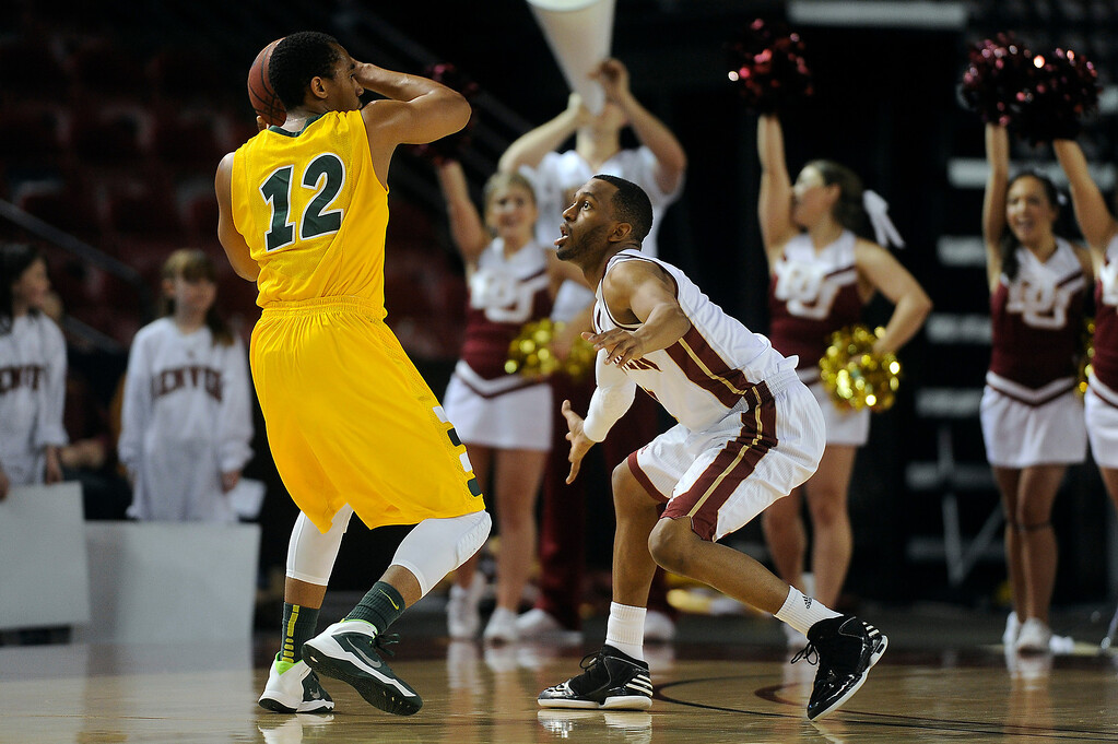 . North Dakota State guard Lawrence Alexander (12) is pressured by University of Denver guard Jalen Love (3) as he drives the ball down court during the first half at Magness Arena in Denver, Colorado on February 1, 2014. (Photo by Seth McConnell/The Denver Post)