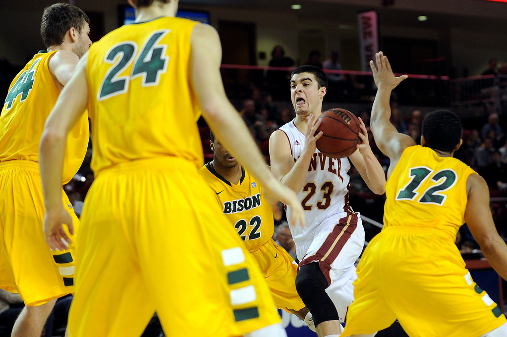 . University of Denver guard Brett Olson (23) splits the North Dakota defense as he drives to the net during the first half at Magness Arena in Denver, Colorado on February 1, 2014. (Photo by Seth McConnell/The Denver Post)