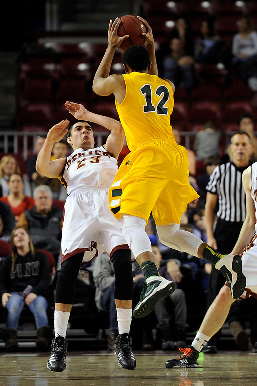 . University of Denver guard Brett Olson (23) falls over backwards after fouling North Dakota State guard Lawrence Alexander (12) as they scrambled for a loose ball during the second half at Magness Arena in Denver, Colorado on February 1, 2014. The Pioneers defeated the Bison 67-63. (Photo by Seth McConnell/The Denver Post)
