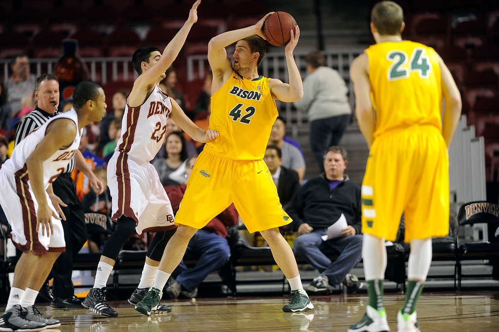 . North Dakota State forward Marshall Bjorklund (42) is pressured by University of Denver guard Brett Olson (23) as he looks for an open teammate during the first half at Magness Arena in Denver, Colorado on February 1, 2014. (Photo by Seth McConnell/The Denver Post)