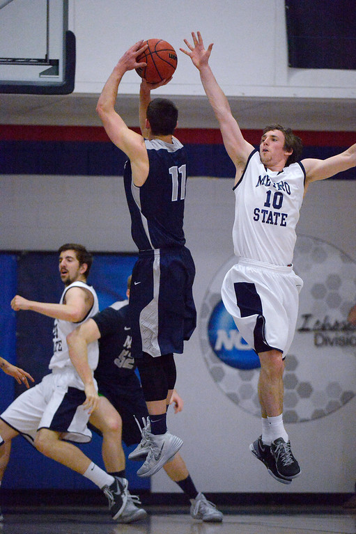 . Colorado Mines\' Brett Green (11) takes a shot past Metro State\'s Mitch McCarron (10) during the first half of the Division ll Men\'s Basketball Championship March 16, 2014 at Auraria Event Center (Photo by John Leyba/The Denver Post)