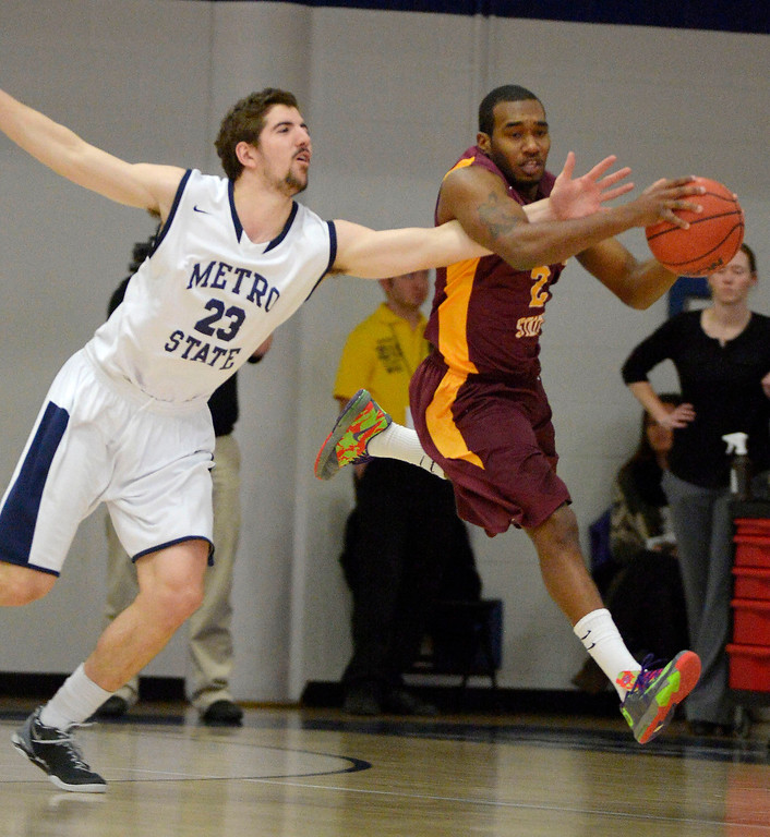 . Metro State Harrison Goodrick (23) reaches in on Midwestern State DeJuan Plummer (2) during the first half March 18, 2014 in the Championship game of the Division ll Men\'s Basketball Championship at Auraria Events Center. (Photo by John Leyba/The Denver Post)