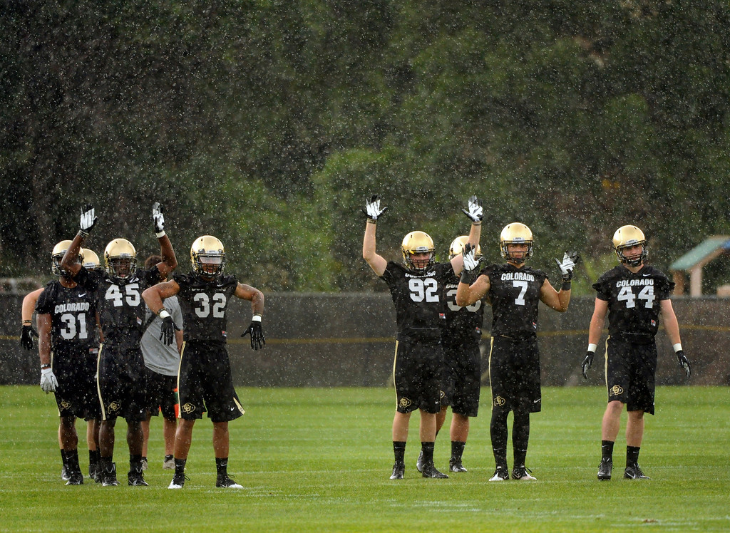 . BOULDER, CO. - AUGUST 06: The rain came down on defensive players as the practice got under way Tuesday. The University of Colorado football team practiced for the first time Tuesday afternoon, August 6, 2013. Photo By Karl Gehring/The Denver Post