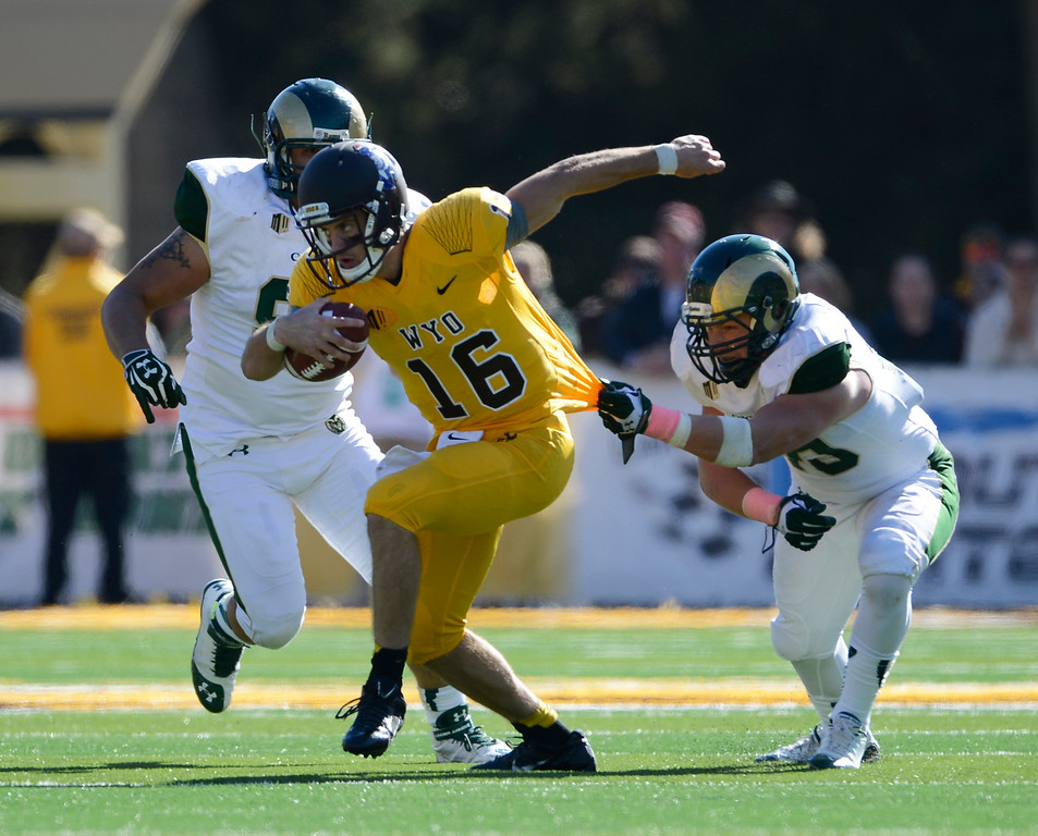 . Colorado State MLB, Max Morgan, right, and nose tackle, Curtis Wilson, left, gang up on Wyoming QB, Brett Smith for a tackle in the third quarter of play at Jonah Field at War Memorial Stadium Saturday, October 19, 2013.  (Photo By Andy Cross/The Denver Post)