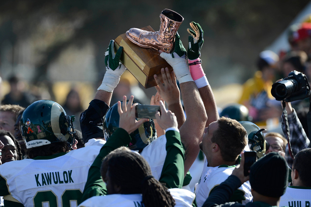 . The Colorado State Rams celebrate their victory over the Wyoming Cowboys hoisting the Bronze Boot at Jonah Field at War Memorial Stadium Saturday, October 19, 2013. Winner of the annual �border war� wins the boot. (Photo By Andy Cross/The Denver Post)